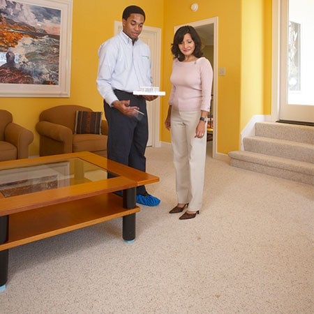 guy and lady standing on carpet talking about service