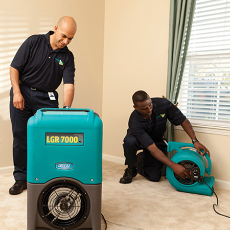 two technicians setting up air movers in home on beige carpet