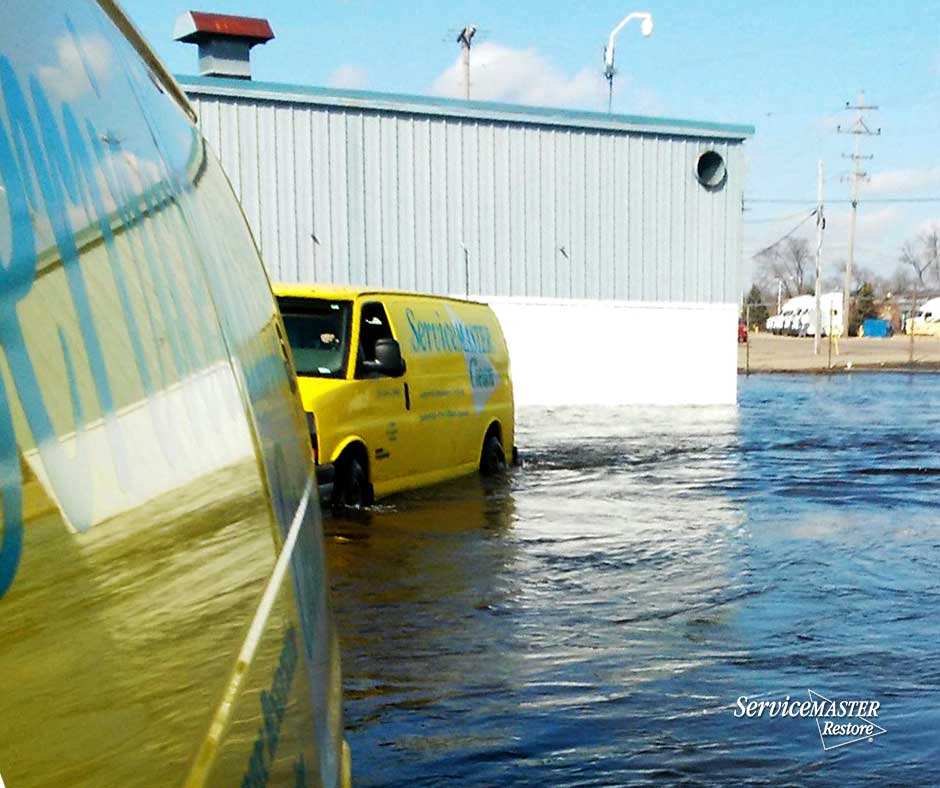 vans halfway in flooded water helping remove water from businesses and homes