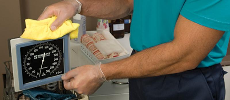 guy cleaning blood pressure gauge in office